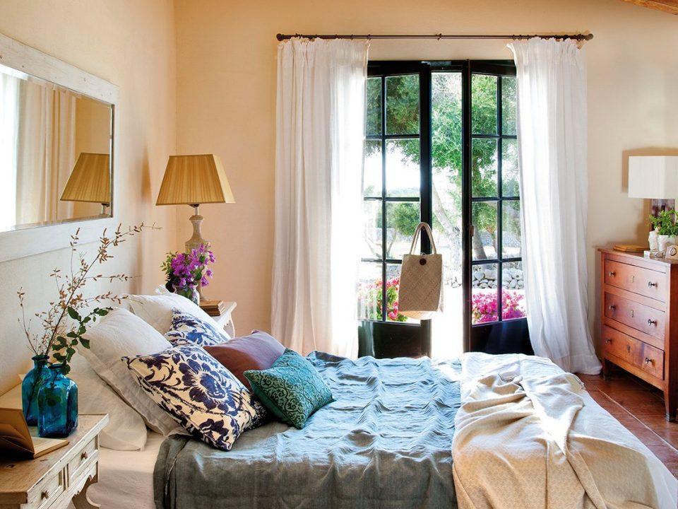 dormitorio_abuhardillado_con_espejo_sobre_el_cabecero_de_la_cama_foto primavera
